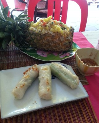 Fresh spring rolls and fried rice in a pineapple